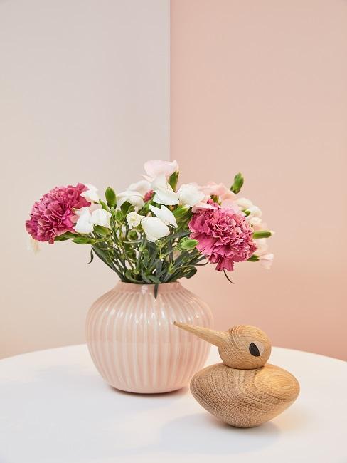 Roze bloempot met klein bosjes bloemen en houten accessoires
