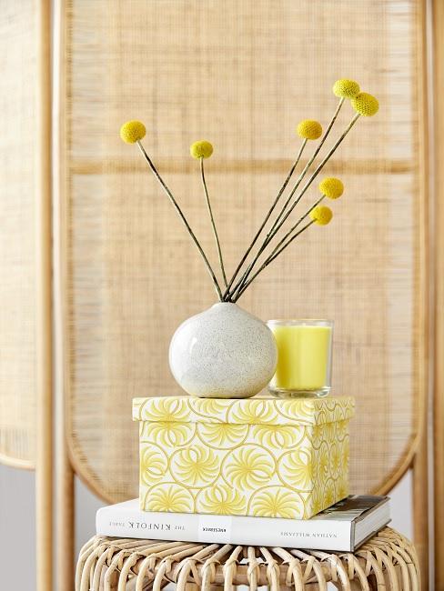 Boho scherm met gele doos en witte vaas met gele bloemen