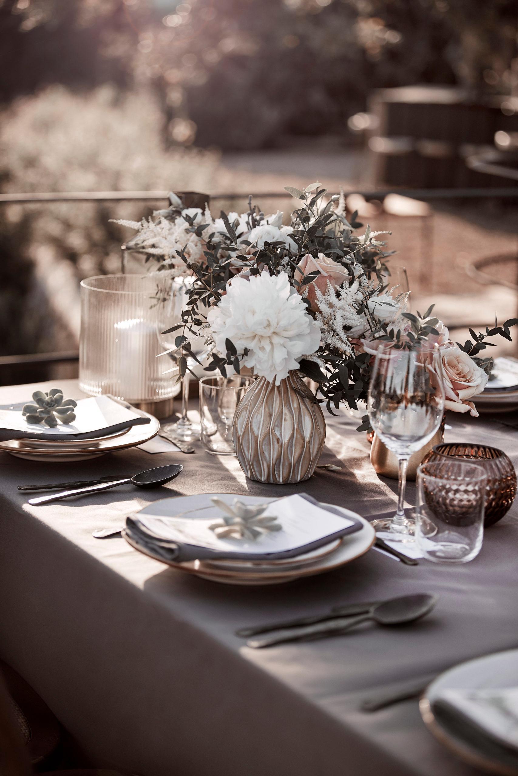 Gedekte bruiloftstafel buiten met veel kaarsen en bloemen als tafeldecoratie in boho stijl