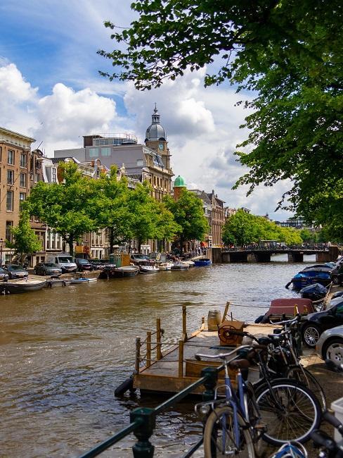 Fietsen aan de kade van een gracht met boten en huizen op de achtergrond Trouwen in het buitenland