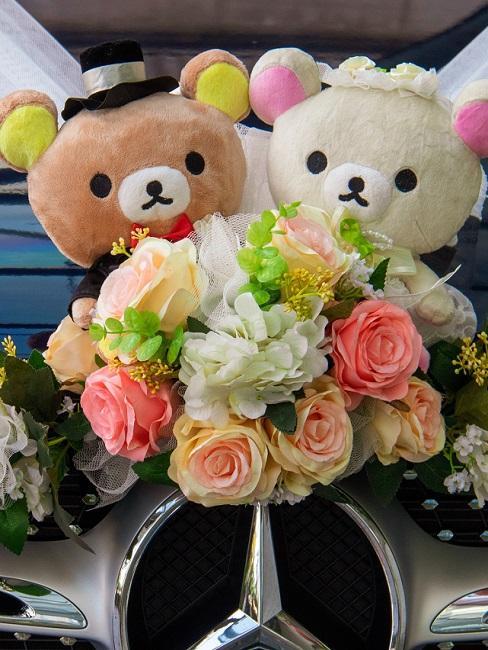 Bruiloft decoratie met bloemen en teddyberen op de auto