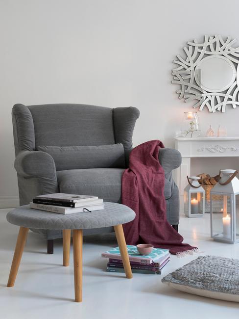 Duży szary fotel z bordowym kocem w jasnym salonie