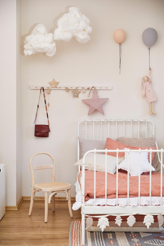 Beżowy pokoik dziecięcy z łożkiem o różowej pościeli i elegemntami dekoracyjnymi