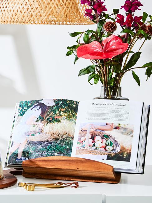 Ksiązka kucharska wystawiona w kuchni, za którą znajduje się dekoracja kwiatowa
