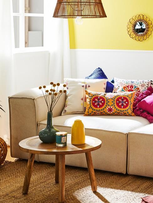 Fragment salon z żółtymi ścianami, jasną sofą, drewnianym stolikiem kawowym oraz poduszkami we wzory etno