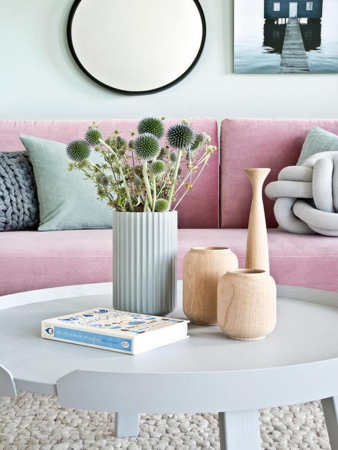 Jasnobłękitny stolik do kawy w salonie sotjący przez różową kanapą