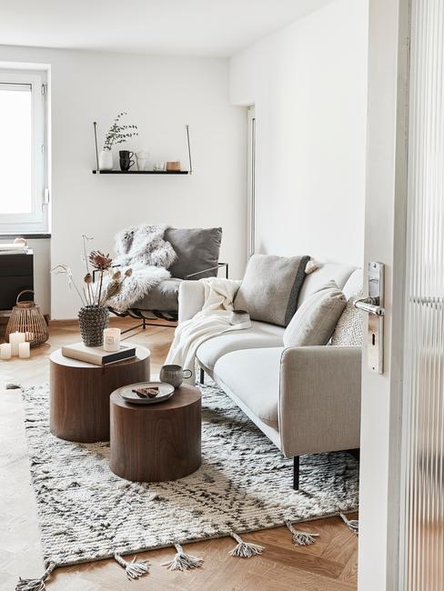Salon w stylu boho z białą kanapą, skórzanymi pufami oraz wzorzystym dywanem