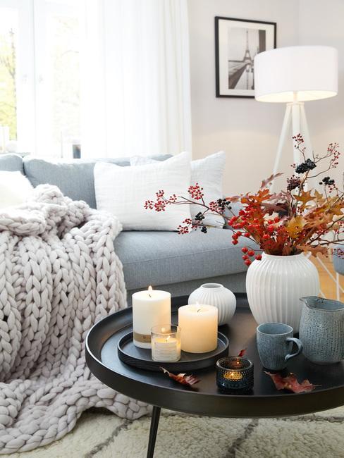 Kremowy salon z niebieską sofą, pledowym kocem oraz czarnym stolikiem kawowym z dekoracjami z gałęzi