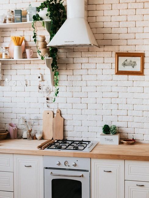 Fragment kuchni z białą, ceglaną ścianą i akcesoriami kuchennymi