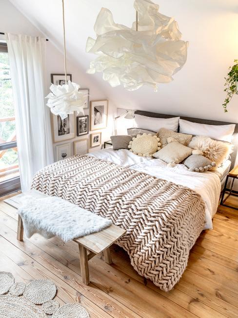 Jasna sypialnia z podwójnym łożkiem, beżową plecowym kocem, poduszkami dekoracyjnymi i lampą chmurą
