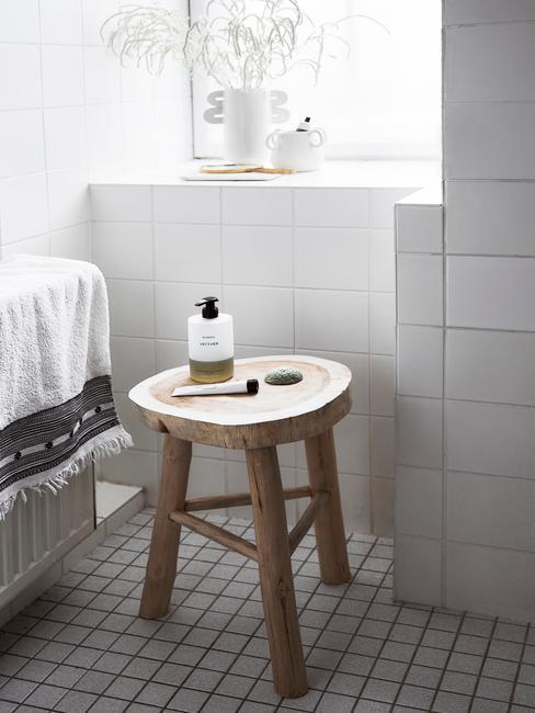 Biała łazienka z wanną oraz drewnianym stołkiem