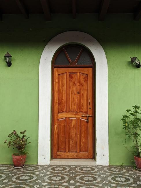 Pistacjowa ściana domu z drewnianymi drzwami