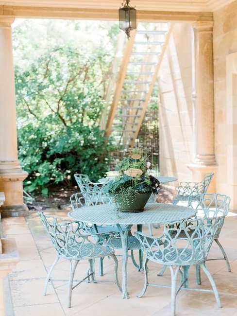 Zadaszony taras z niebieskimi meblami ogrodowymi
