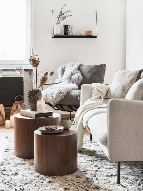 Fragment salonu z białą kanapą, drewnianymi stolikami oraz szarym fotelem z kocem
