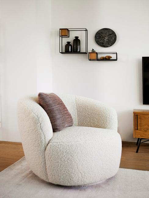 Biały salon z fotelem wykonanym z miękkiego materiału i zegarem na ścianie