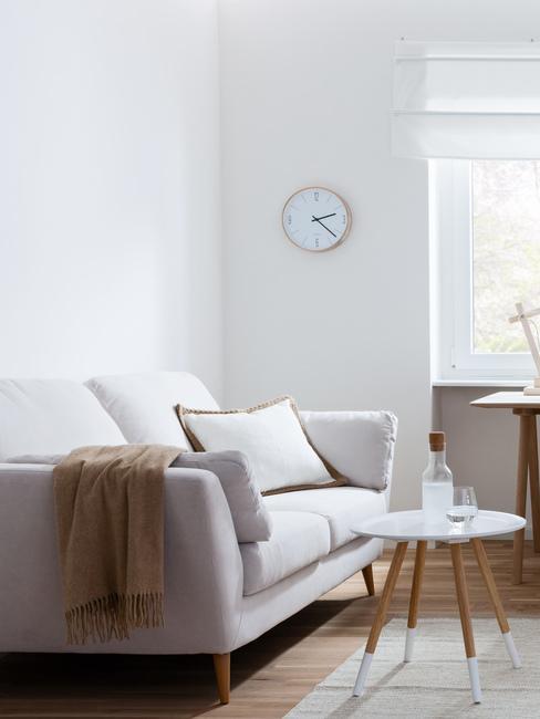 Salon z stylu nowoczesnym z asną kanapą, drewnianym stolikiem oraz zegarem na ścianie