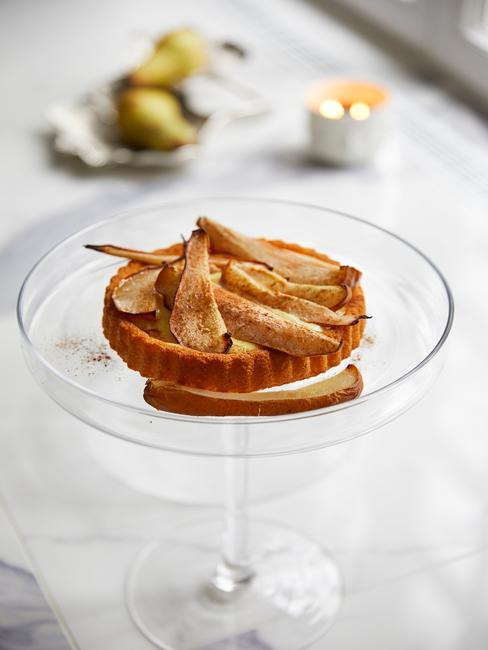 Mała tartaletka z gruszkami umieszczona w kieliszku od martini