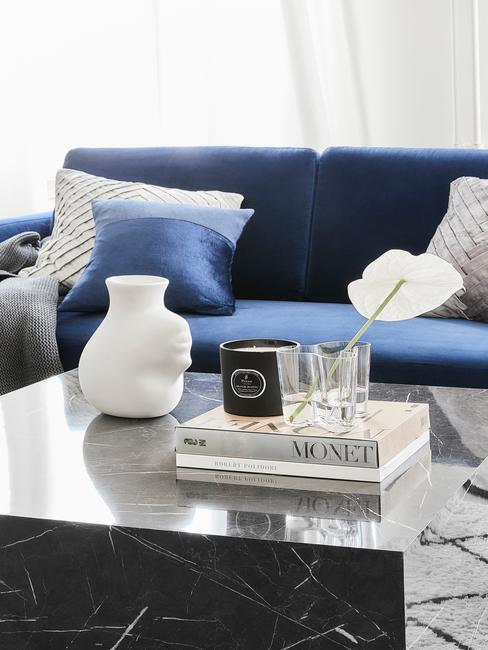 Sofa w kolorze kobaltu obok niej czarny marmurowy stolik z książką albumową