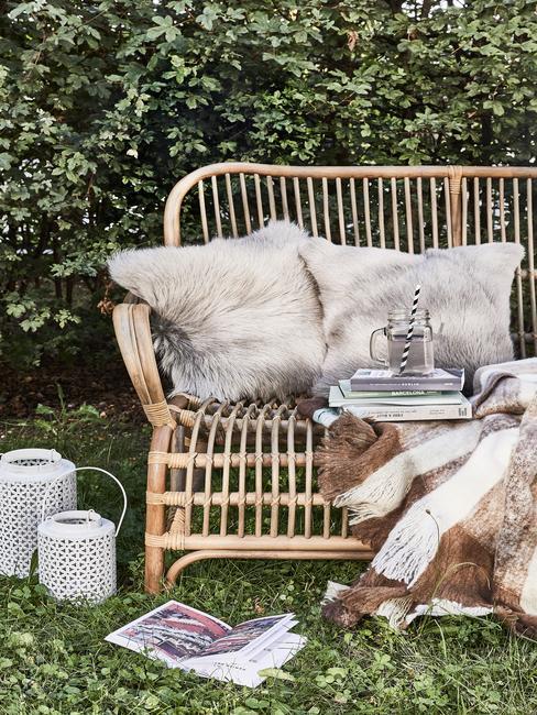 Rattanowa ławeczka z dwoma poduszkami w małym ogrodzie