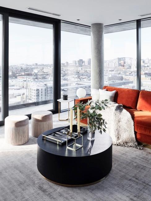 Nowoczesny salon z czarnym, okrągłm stolikiem kawowym, dwoma pufami oraz pomarańczową sofą