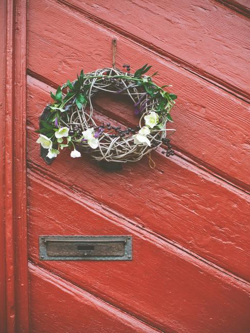 Wianek na drzwi wykonany z gałązek powieszony na czerwonych drzwiach
