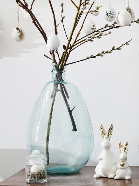 Gałązki wierzby ustawione w niebiekim wazonie obok którego stoją wielkancocne zajączki