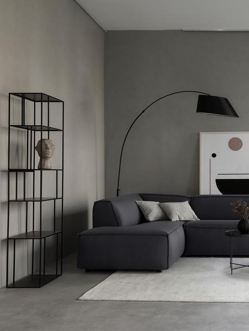 Fragment salonu z narożną kanapą, dużą, stojącą lampą oraz czarnym, metalowym regałem z dekoracjami w stylu industrialnym