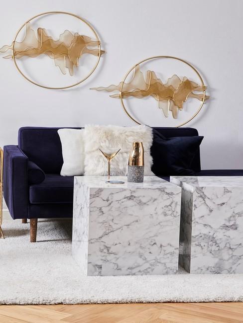 Salon w stylu minimalistycznym z kanapą, stolikami kawowymi oraz metalowymi dekoracjami na ścianę