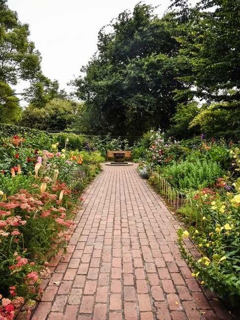 Świeżka pomiędzy rabatami kwiatowymi w ogrodzie w stylu francuskim