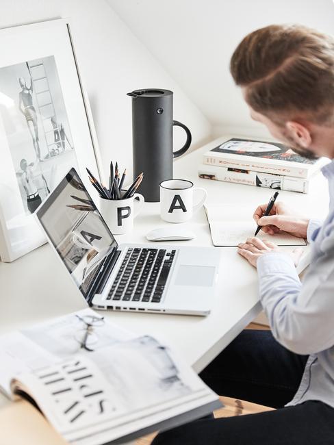 Mężczyzna pracujący z domu i siedzący przy białym biurku z komputerem z kubkami, czajnikiem oraz książkami