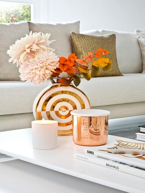Salon z sofą i białym stolikiem, na którym znajduje się wazon z kwiatami w kształcie piłki