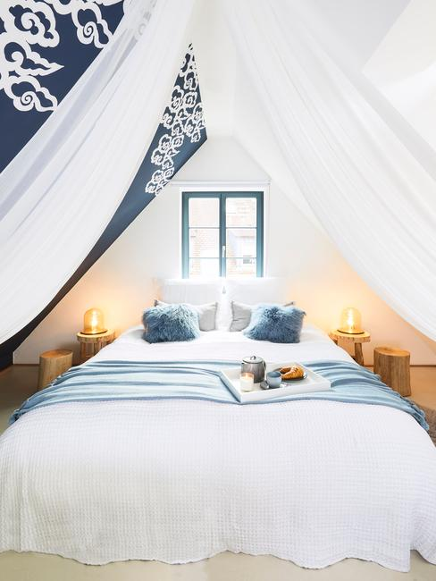 Biała sypialnia z jedną niebieską ścianą, niebieskimi poduszkami i białym baldachimem