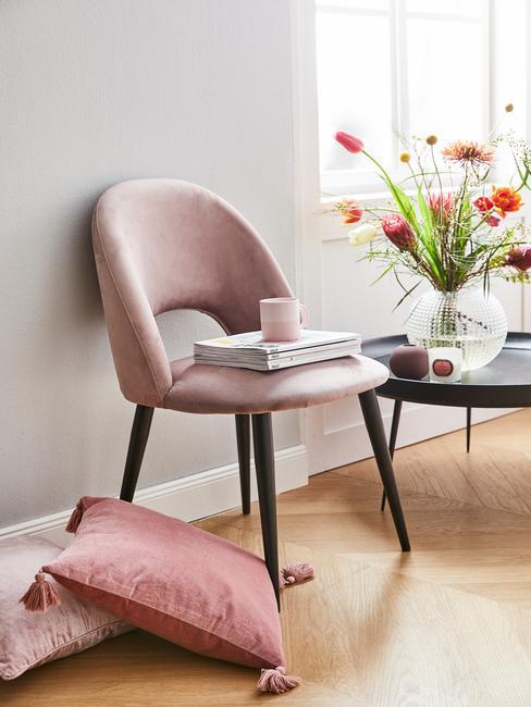 Fragment salonu z różowym krzesłem, poduszką na podłodze oraz czarnym stolikiem z wazonem kwiatów