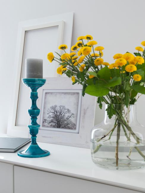 Biała komoda z niebieskim świecznikiem, ramkami ze zdjęciami oraz szklanym wazonem z kwiatami