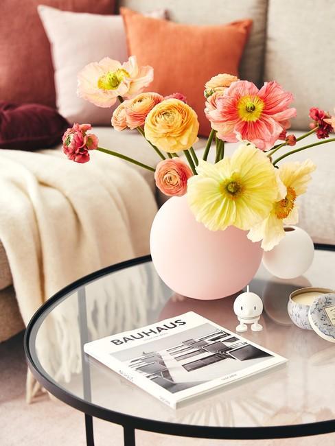 Zbliżenie na szklany stolik z różowym wazonem z kwiatami, w tle jest szara sofa z kolorowymi poduszkami
