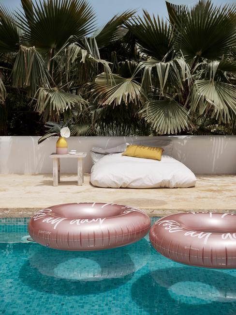 Poduszka oraz stolik lezący przy basenie ogrodowym