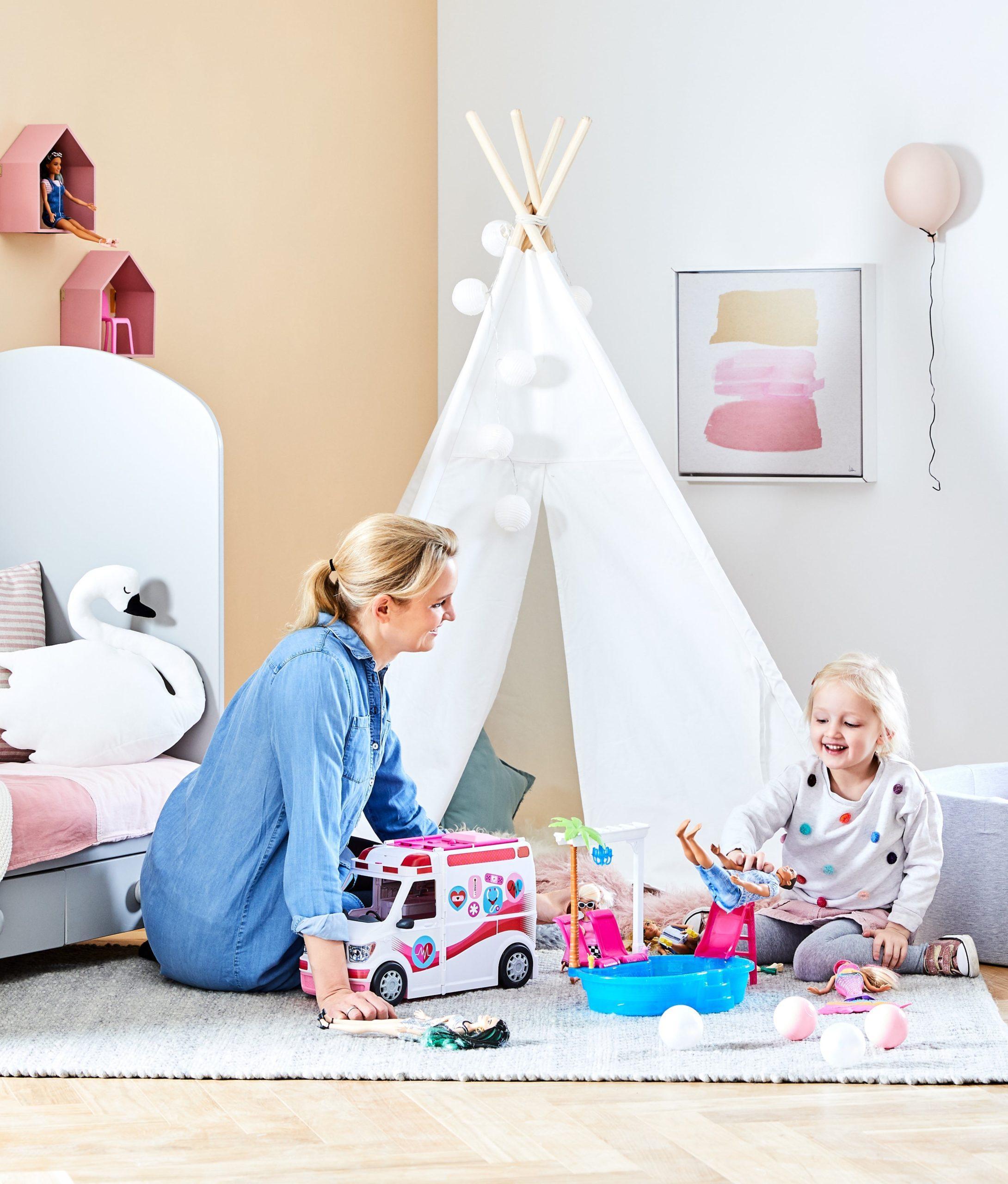 Mama z córką siedzące na podłodze w pokoju dziecięcym