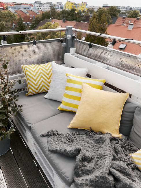 Zbliżenie za sofę wykonaną z palet, na której leżą szare poduszki do siedzenia oraz biało-żółte poduszki dekoracyjne