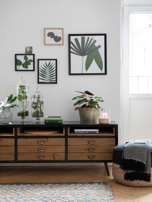 Drewniana komoda w salonie o beżowych ścianach, na których wisi galeria ilustracji