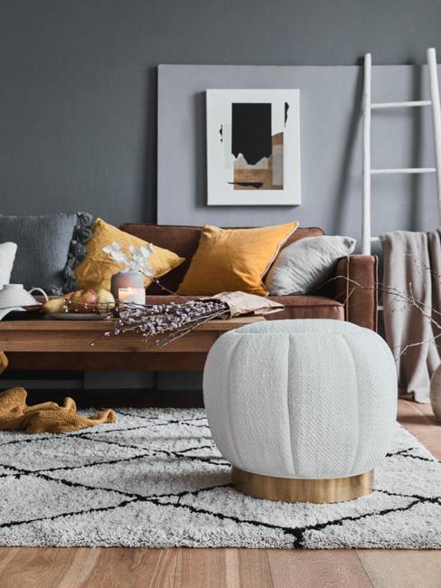 Wnętrze salonu ze skórzaoną sofą, drewnianym stolikiem kawowym, dywanem oraz białym pufem