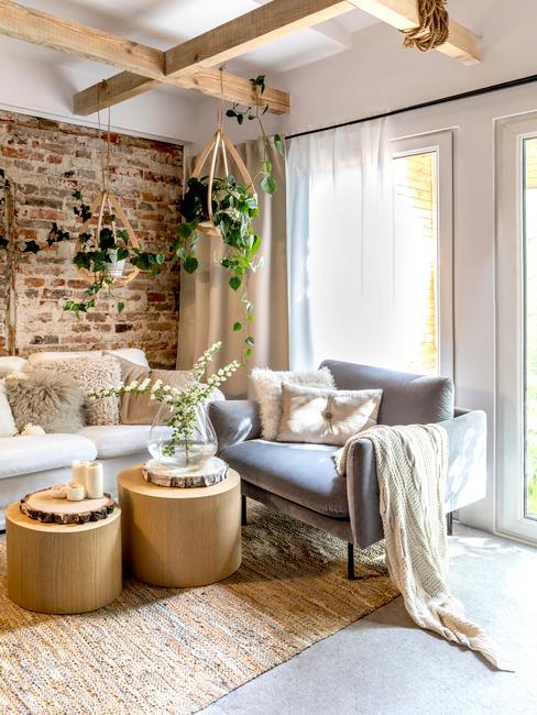 Salon z ceglaną ścianą, drewnianymi stolikami kawowymi, fotelem, sofą oraz roślinnością