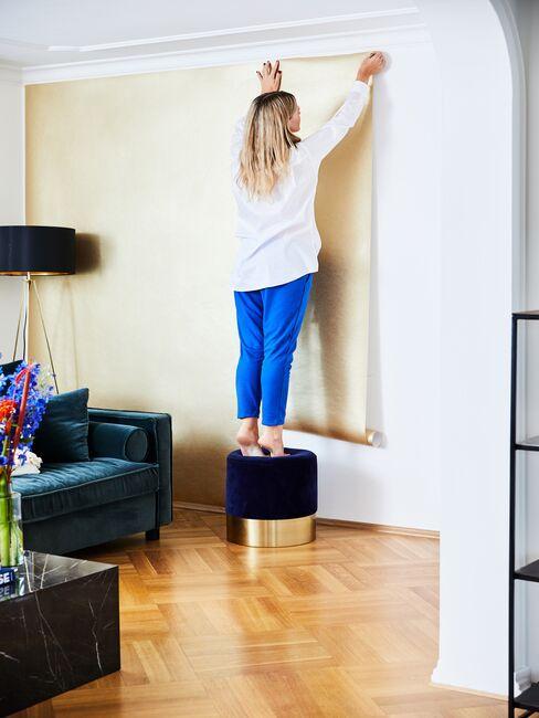 Kobieta kładząca złotą tapetę na ścianie w salonie