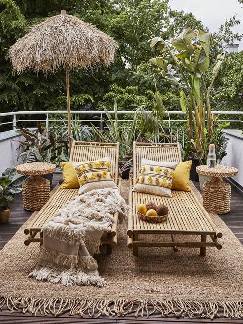 Dwa leżaki, parasol oraz rattanowe stoliki na balkonie