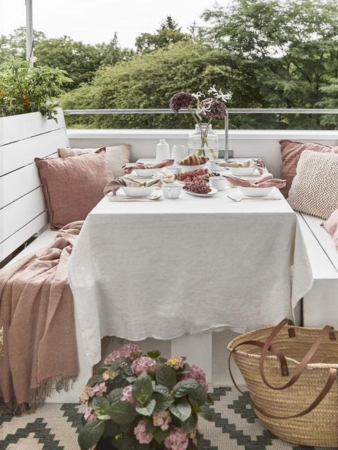 Balkon z dwoma ławkami oraz nakrytym stołem