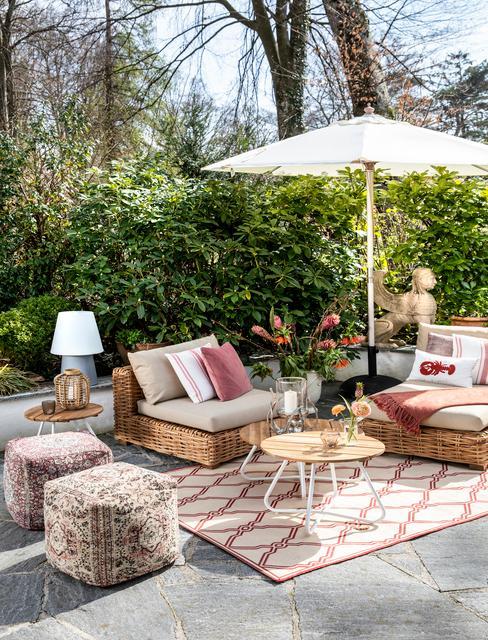Taras przed domem z fotelami z wikliny, stolikiem kawowym, parasolem oraz pufami