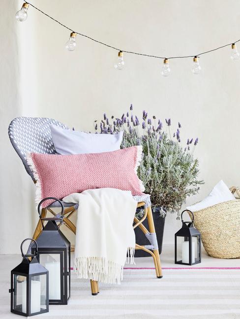 Tragment tarasu z drewnianym fotelem, poduszkami, latarenkami na podłodze oraz doniczką lawendy w tle