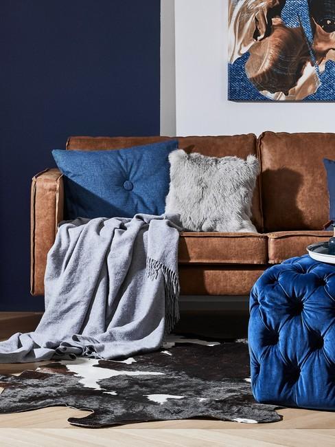 Salon z brązową kanapą, kobatlową ścianą oraz dodatkami w postaci pufu oraz poduszek