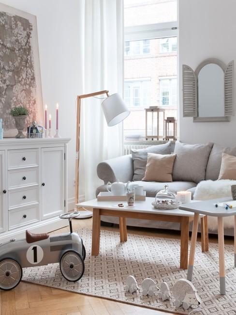 Salon w stylu shabby chic z białą komodą, drewnianym stolikiem oraz szarą sofą