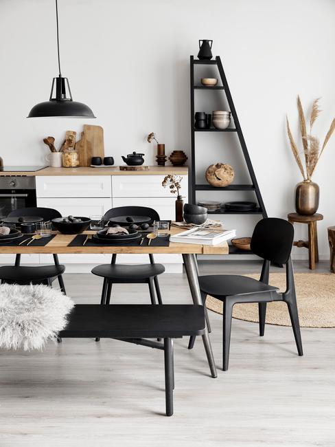 Kuchnia połączona z jadalnią, z drewnianymi meblami, czarnymi miejscami do siedzenia oraz dekoracjami
