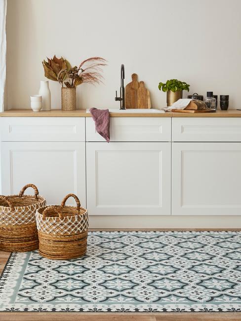 Biała kuchnia z drewnianym blatem, białymi frontami szafek, orientalnym dywanem oraz rattanowymi koszami